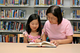 Mother reading with daughter in library